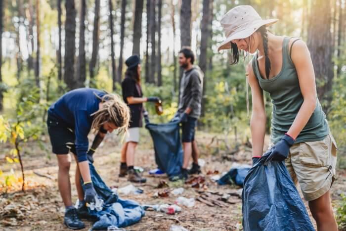 Група приятели, почистваща горите от изхвърлени боклуци