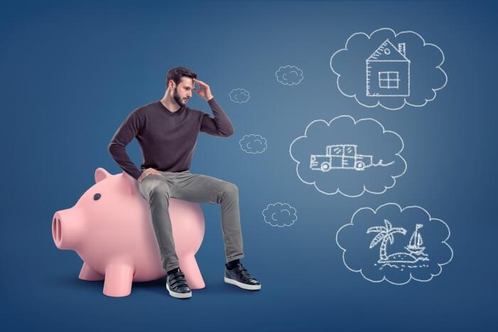 Човек, седнал върху голяма касичка-прасе, който има нужда от парични средства