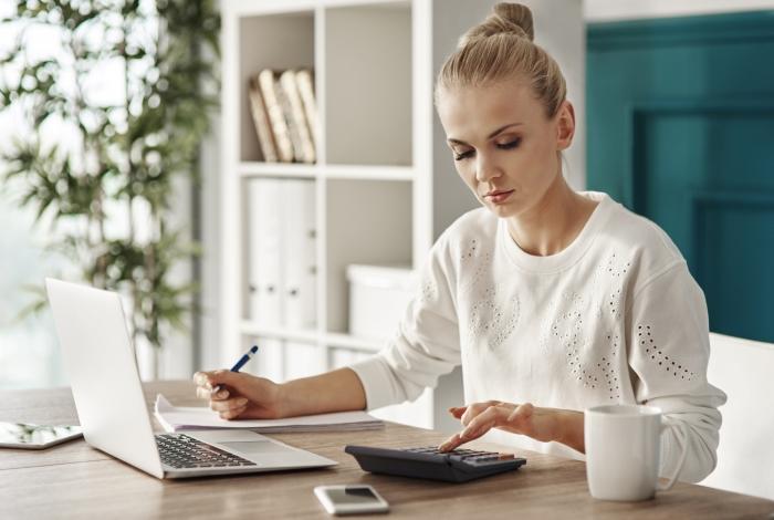 Жена, която пресмята разходите си, за да разбере дали ще име нужда от теглене на бързи заеми за непредвидени сметки