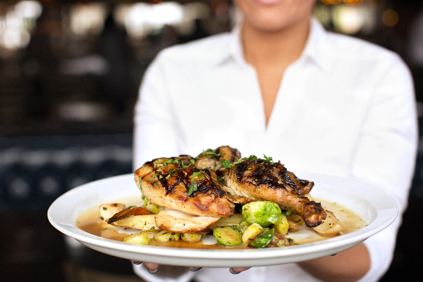 waitress holding plate of grilled chicken