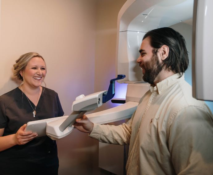 Photo of a Smile Solutions of Baltimore team member with a patient at a digital scanner