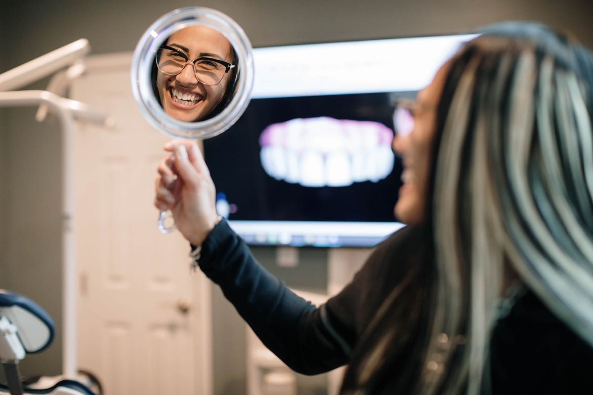 Photo of a patient holding mirror, smiling