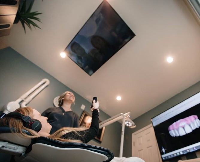 Photo of a patient comfortable in a dental chair watching tv