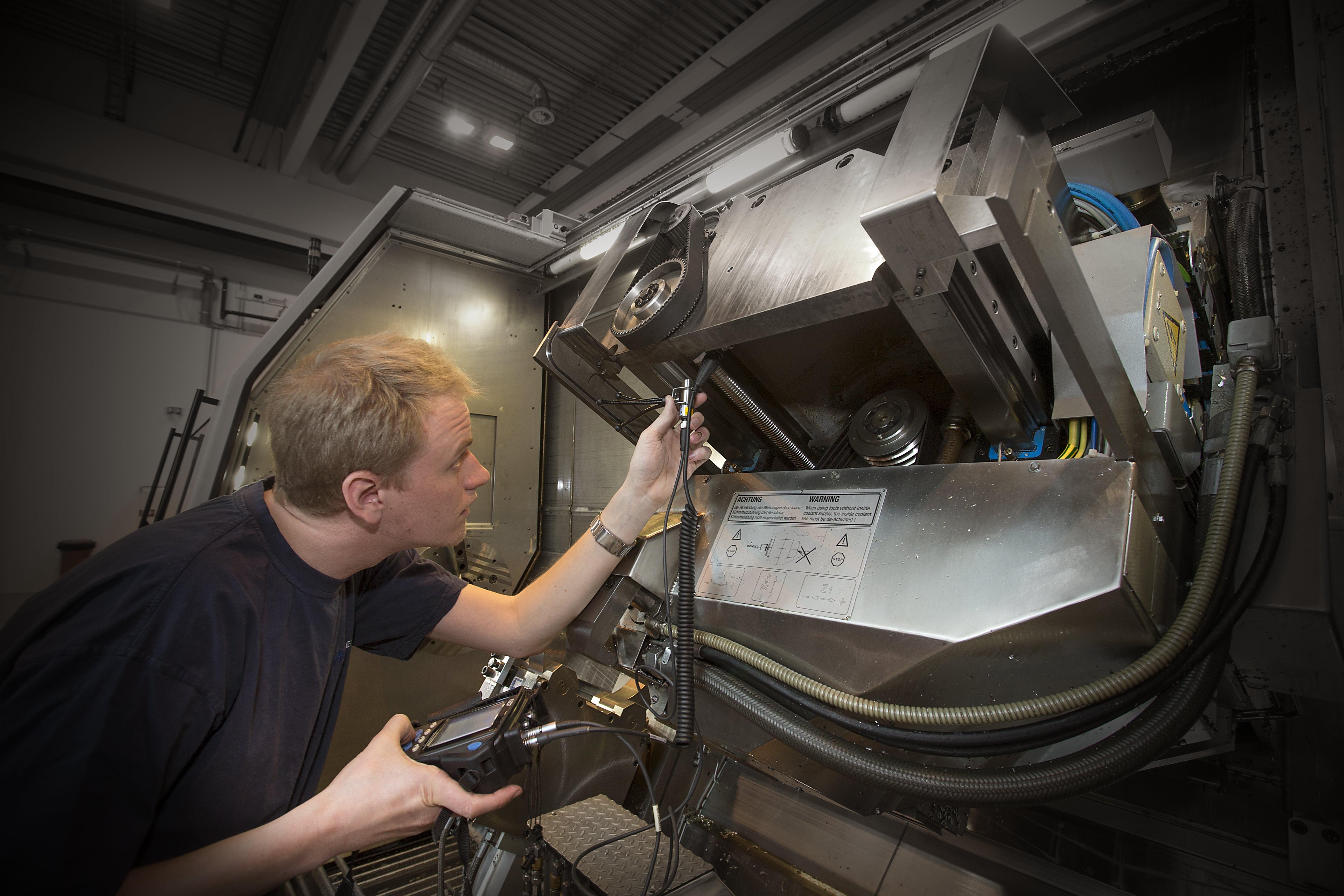 En ansatt jobber med måleinstrument på en maskin
