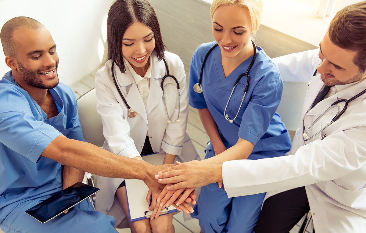 Four healthcare providers putting their hands together.
