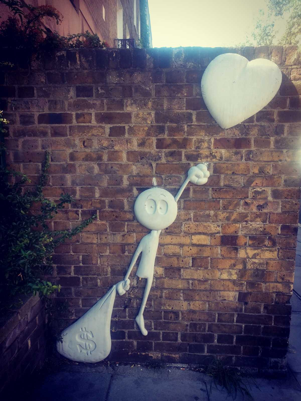 Graffiti of man trying to float away on love heart but weighed down by bag of money