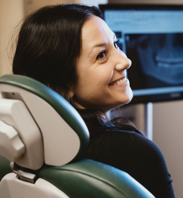 Photo of a patient in the dental chair smiling