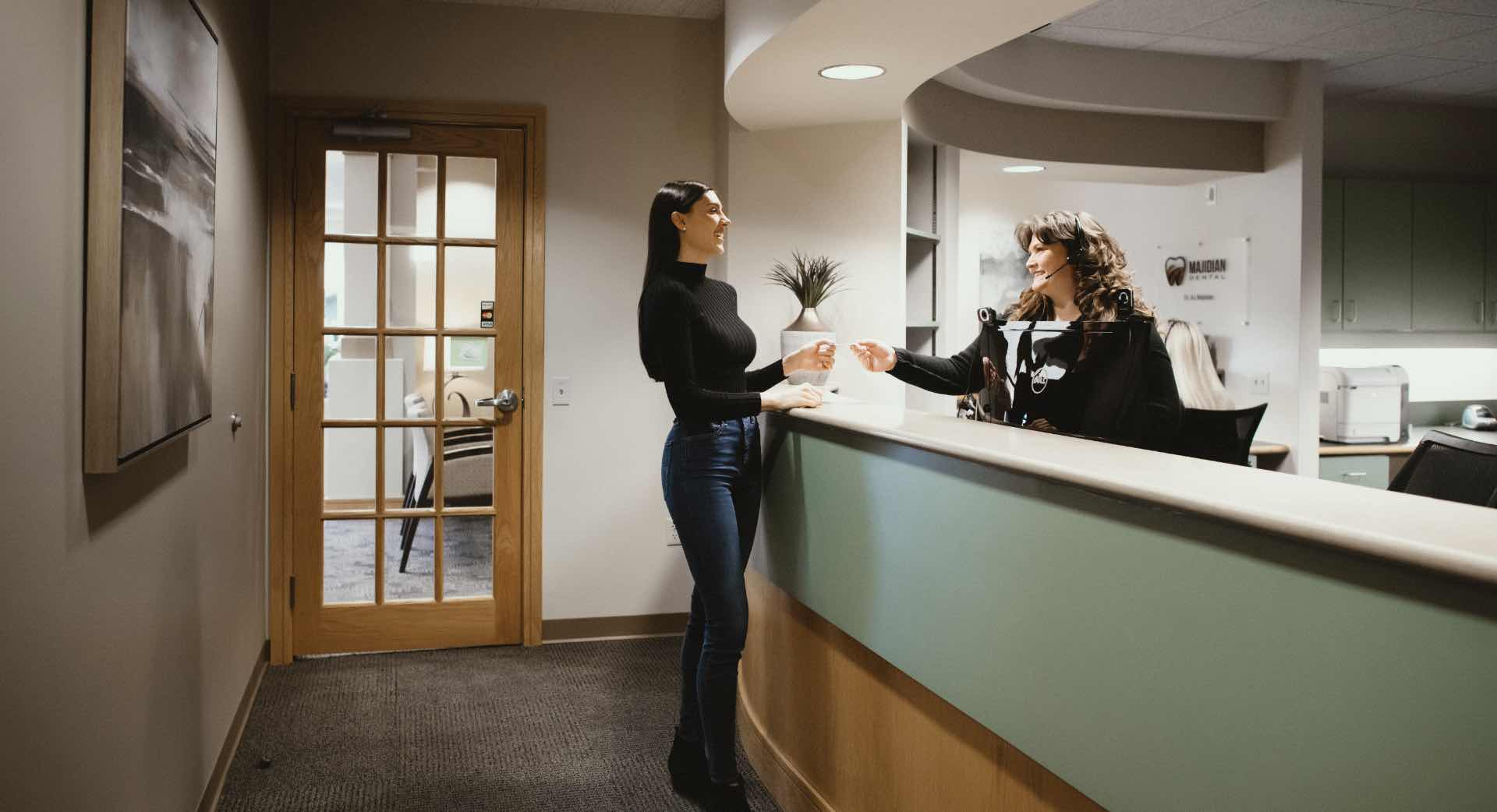 Photo of a Majidian team member assisting a patient at the front desk