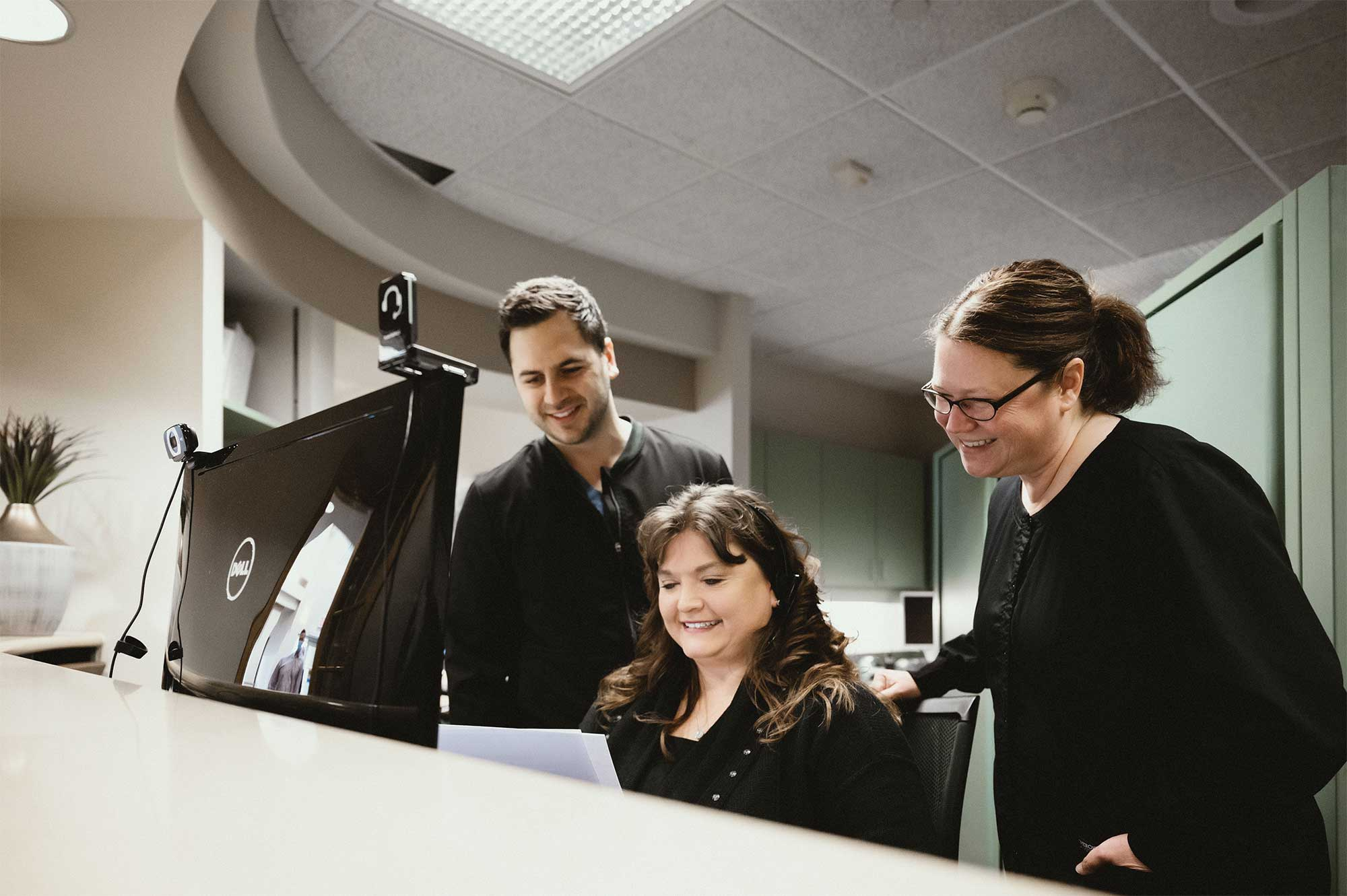 Photo of Dr. Majidian and two team members working together on a computer