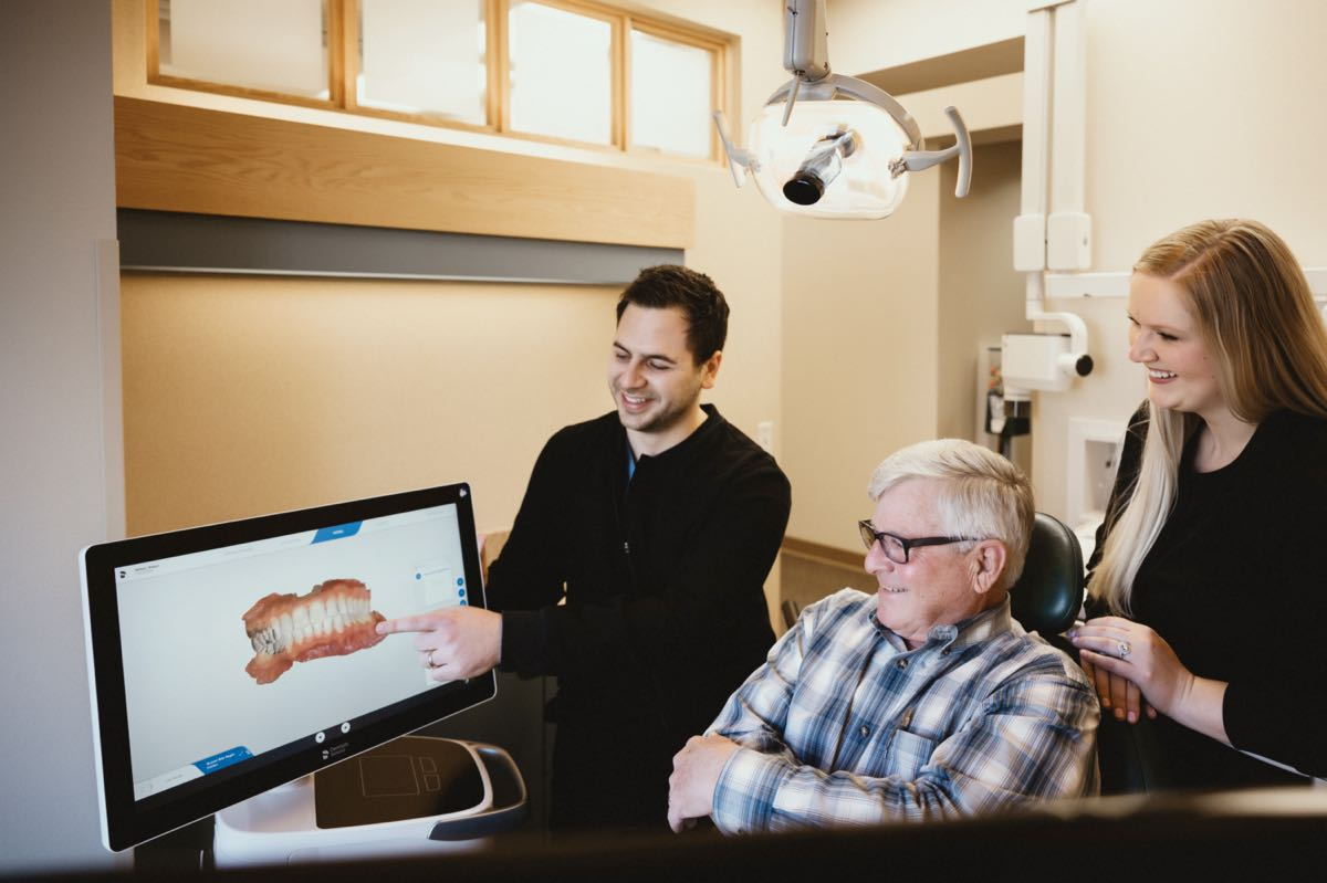 Photo of Dr. Majidian reviewing digital scans with a patient in the dental chair