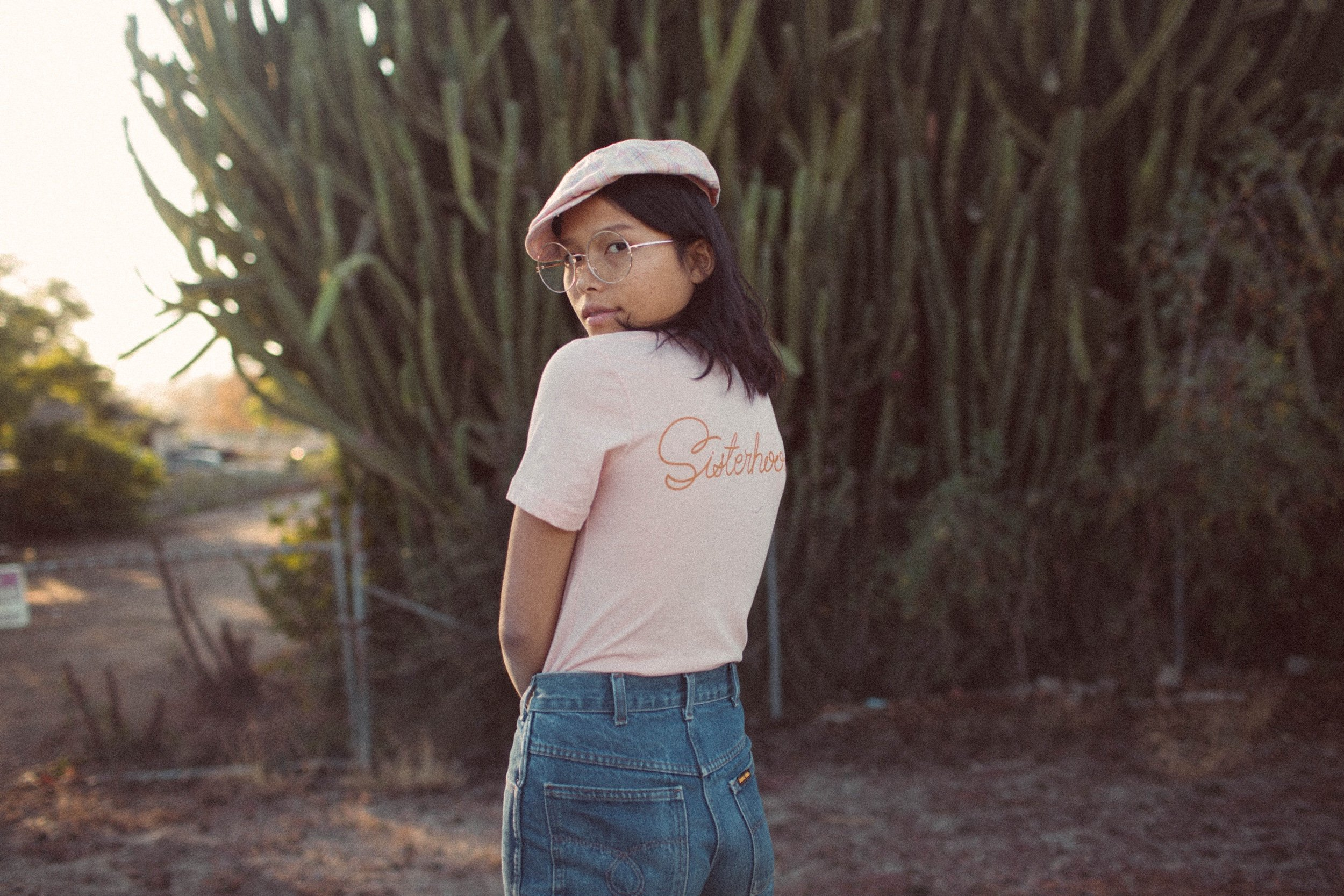 Image of a model wearing a hat and a t-shirt looking back over her shoulder against a background of trees