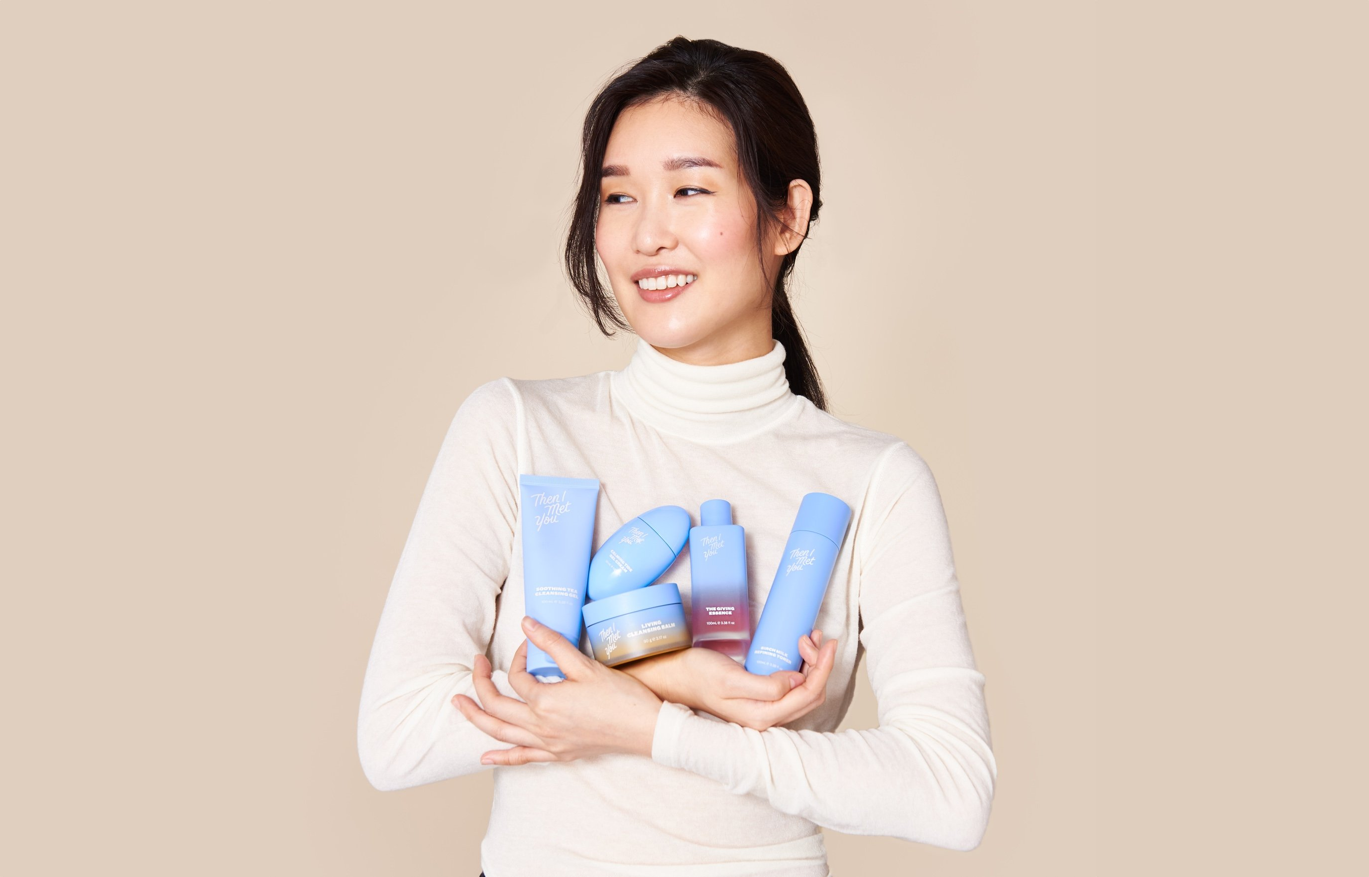 Portrait of Charlotte Cho holding skincare products