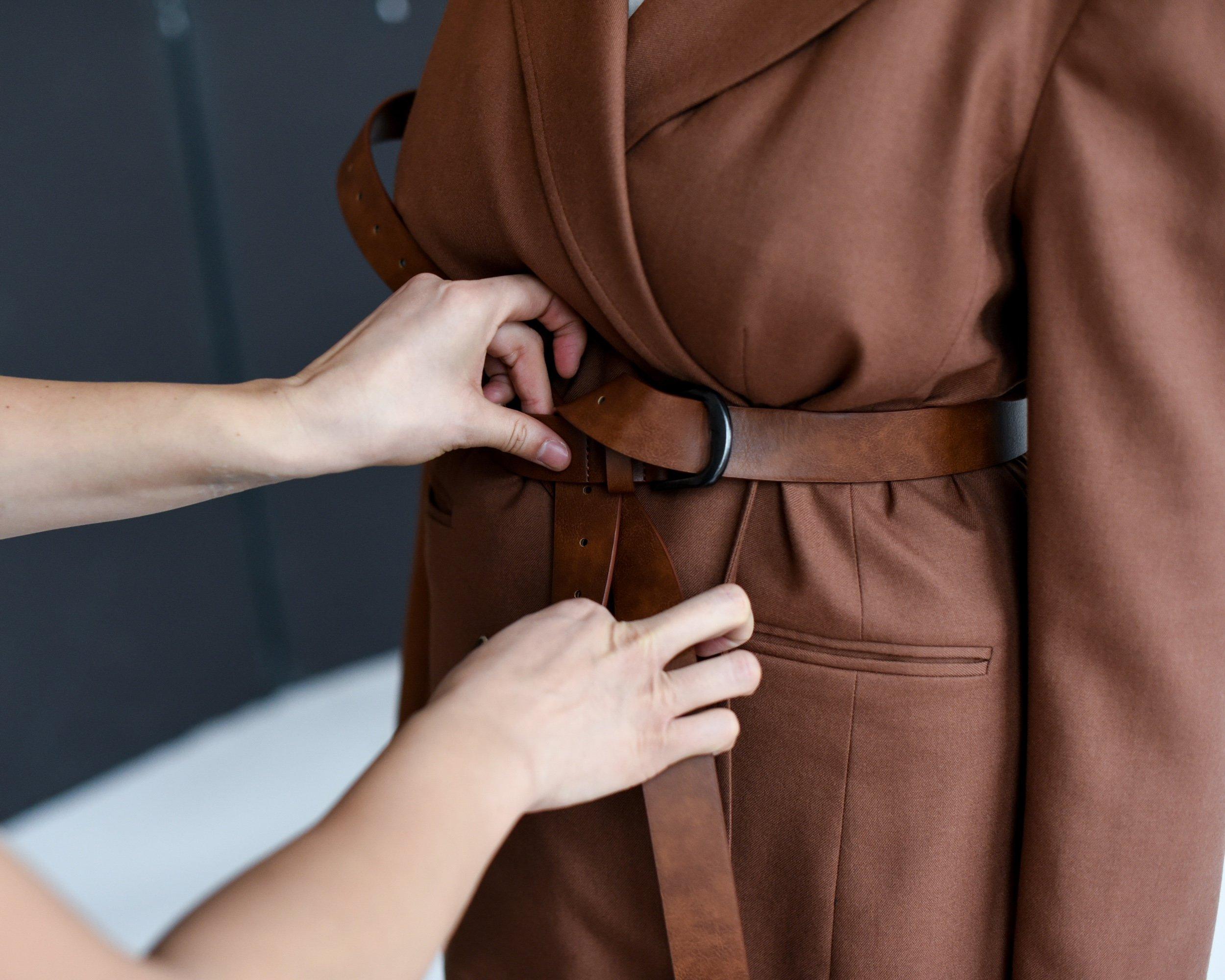 Hands adjust the belt of a brown trench coat