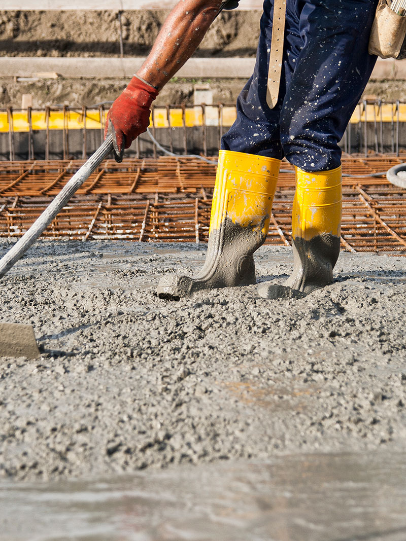 A worker smoothing out freshly laid concrete