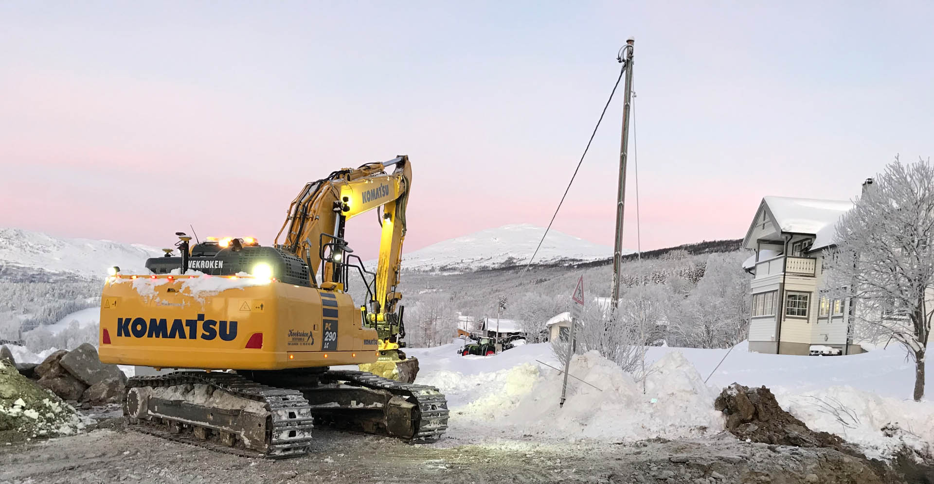 Bilde av en gravemaskin som graver på vinteren.