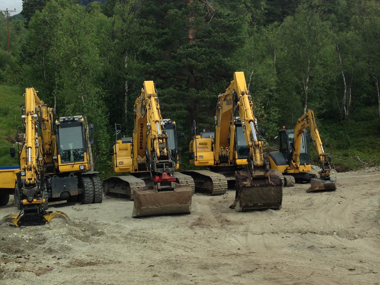 Bilde av fire gravemaskiner i en rekke.