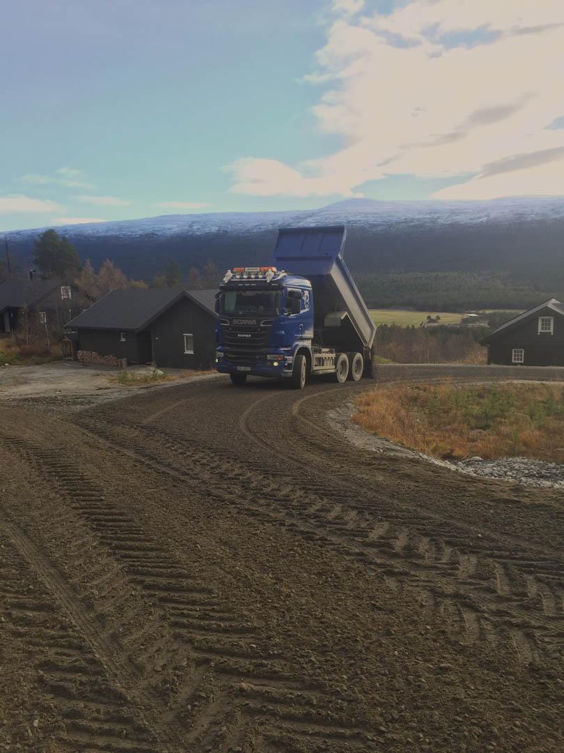 Bilde av en lastebil som legger grus på en vei.