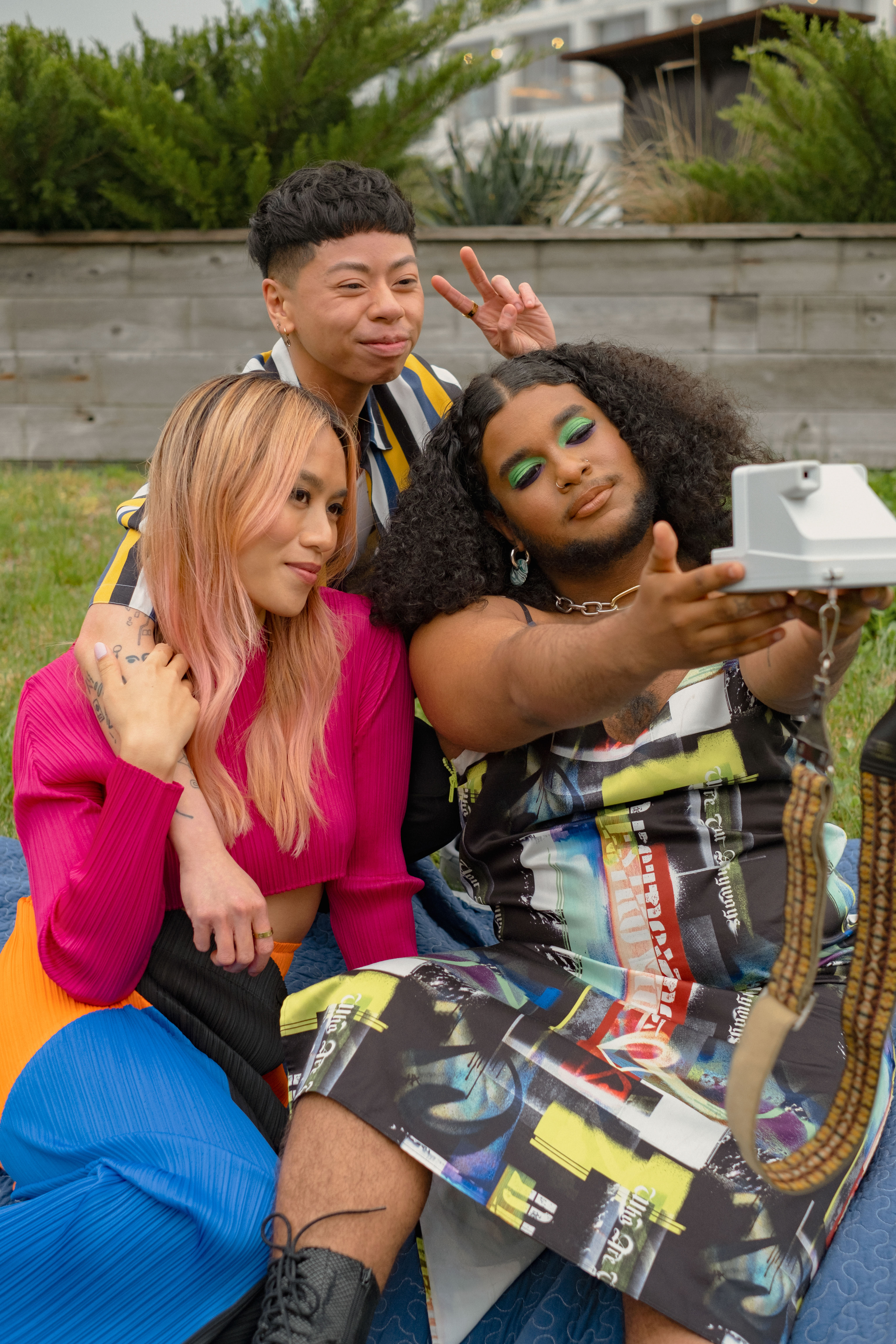 Three friends of varying genders taking a selfie in a park with a polaroid camera