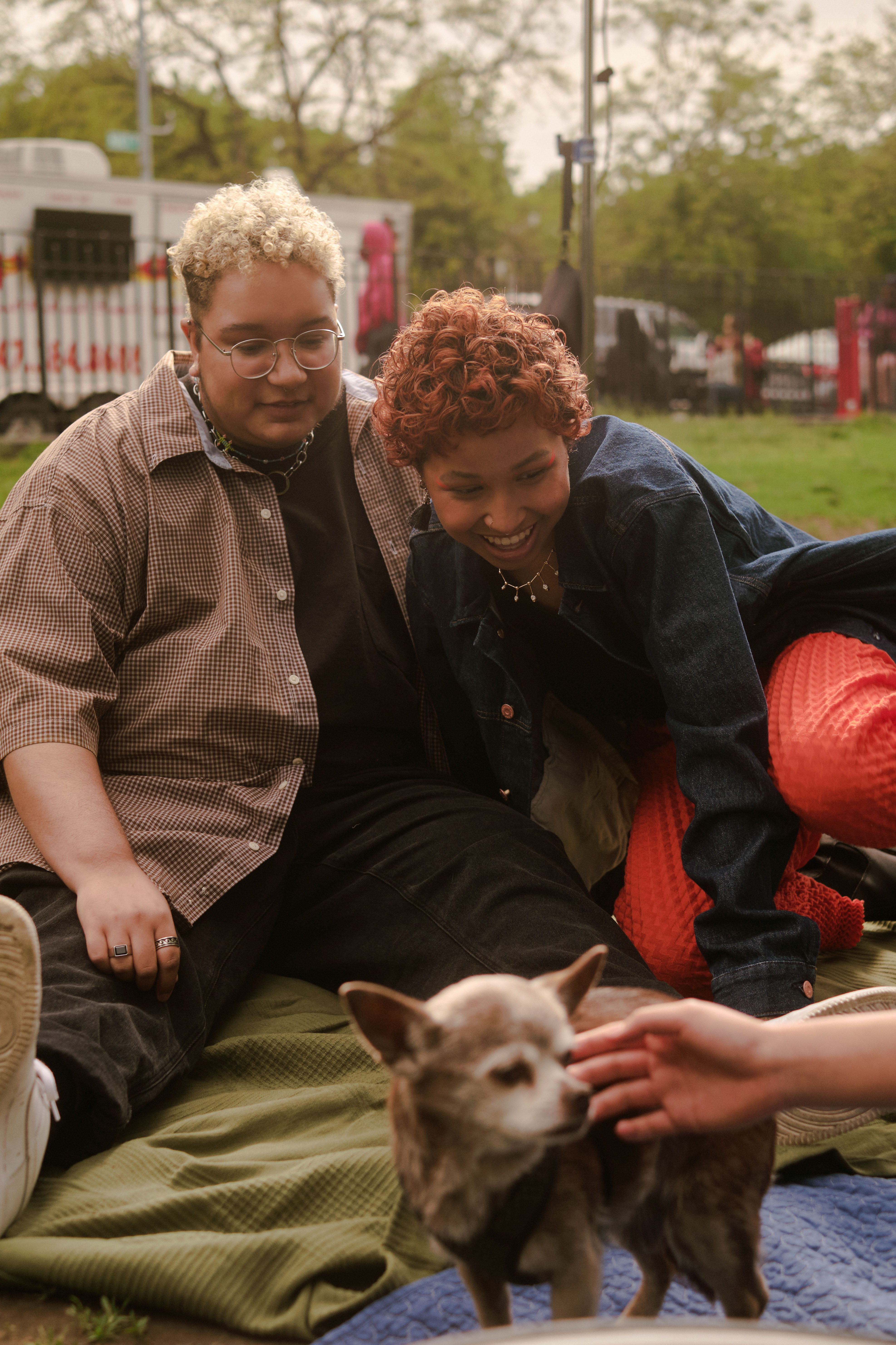 A trans couple hanging out with a dog at the park