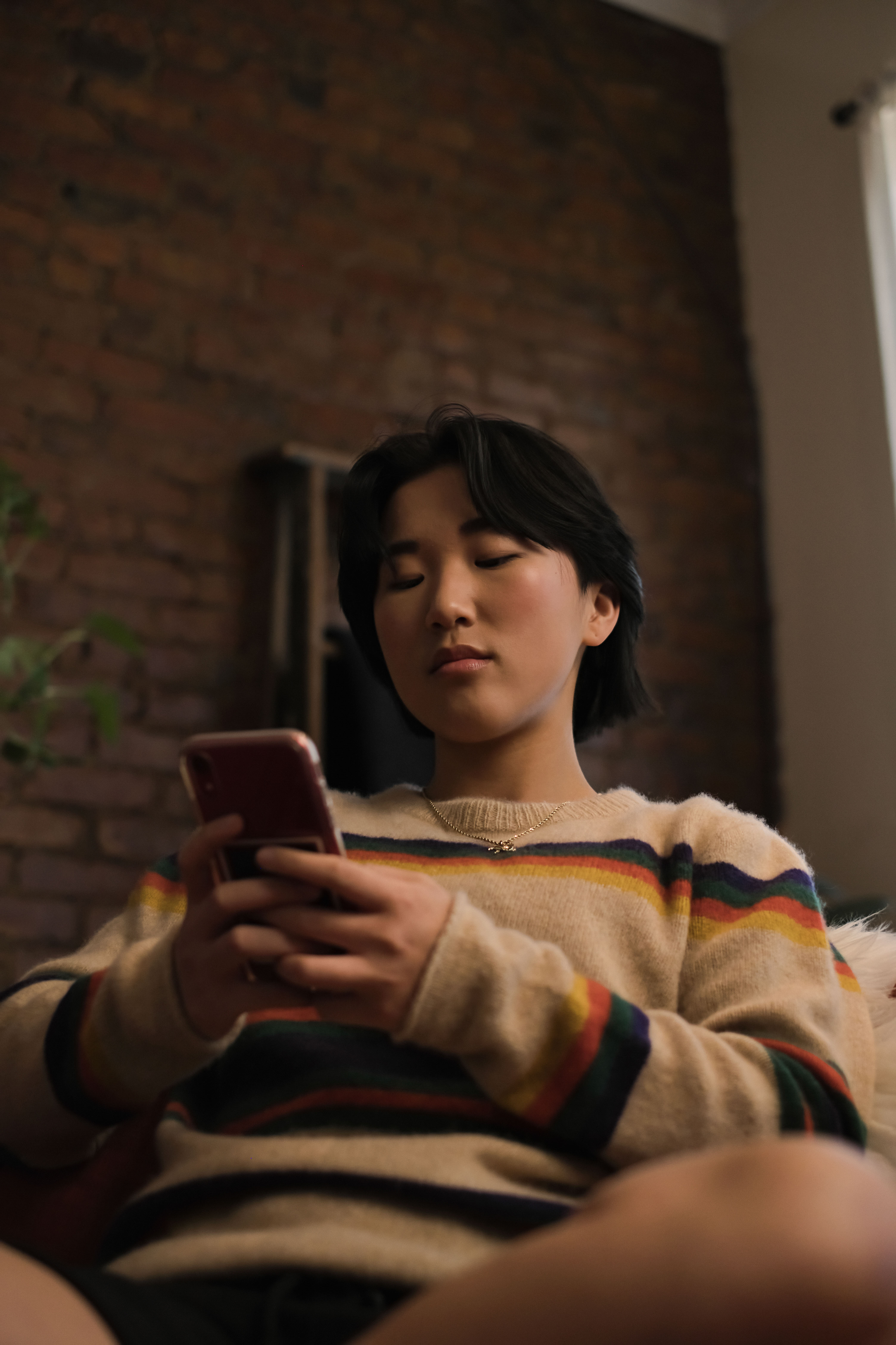 A non-binary person looking at a cellphone