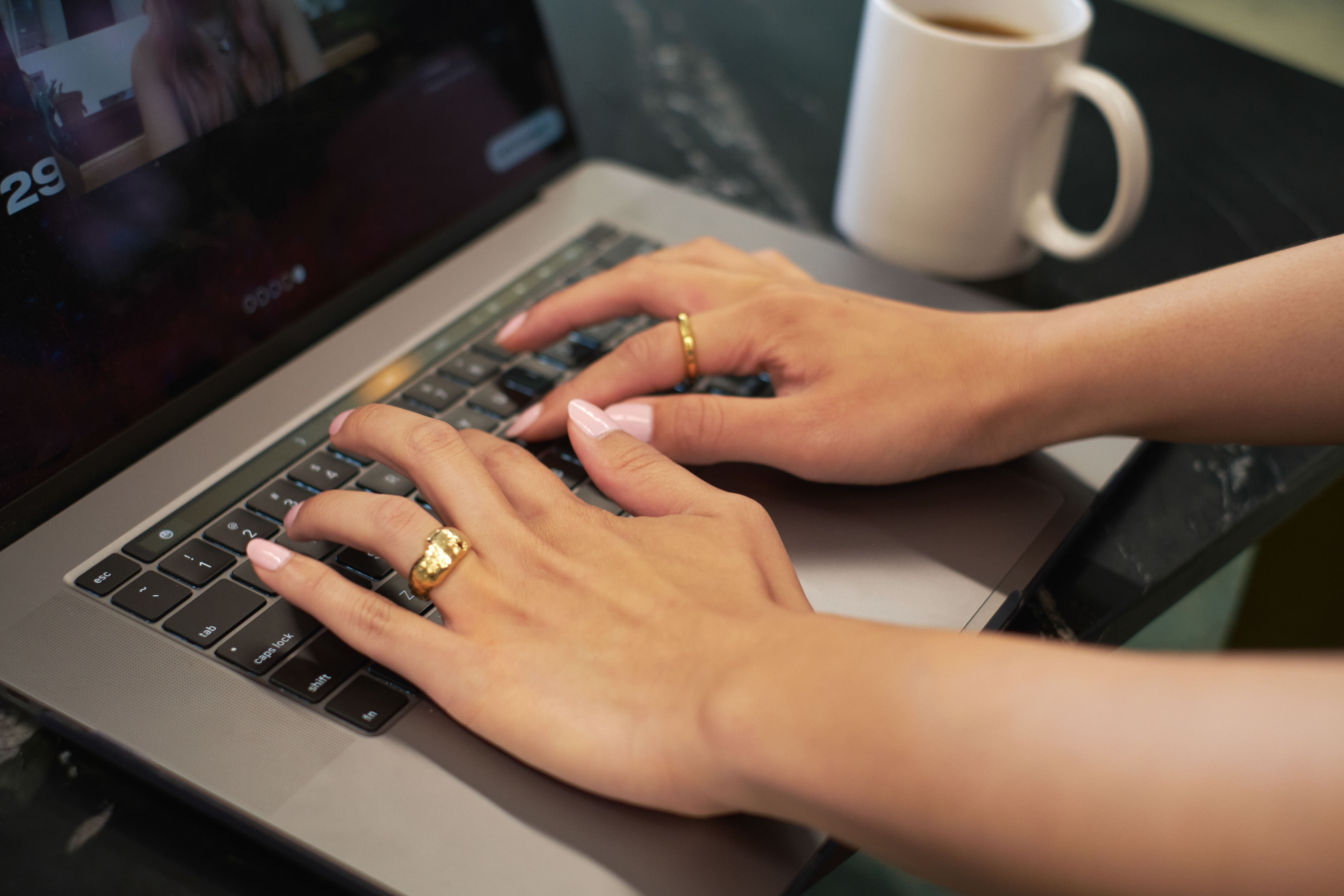 Close-up of a transfeminine person using a keyboard