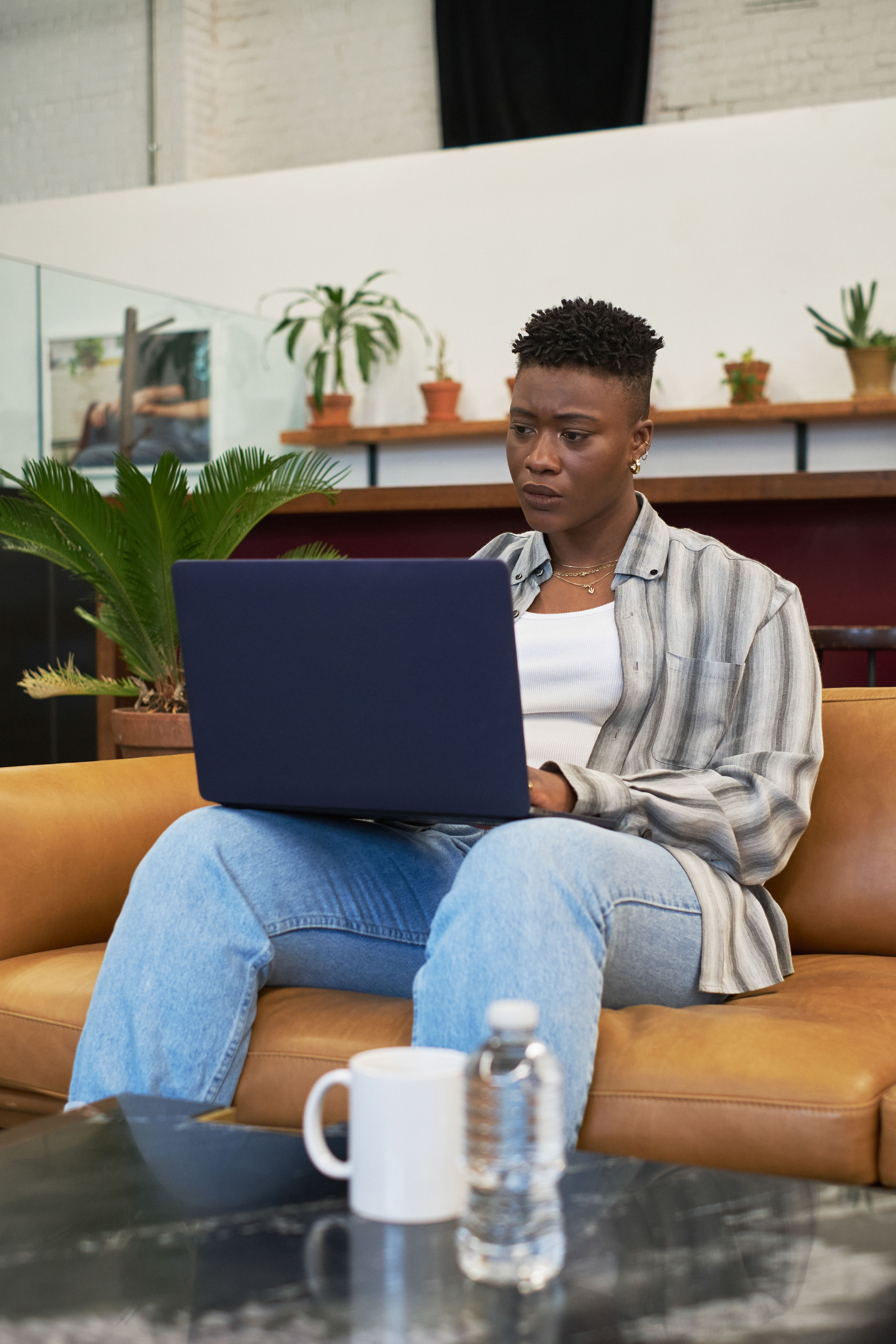 A non-binary person using a laptop at work(2)