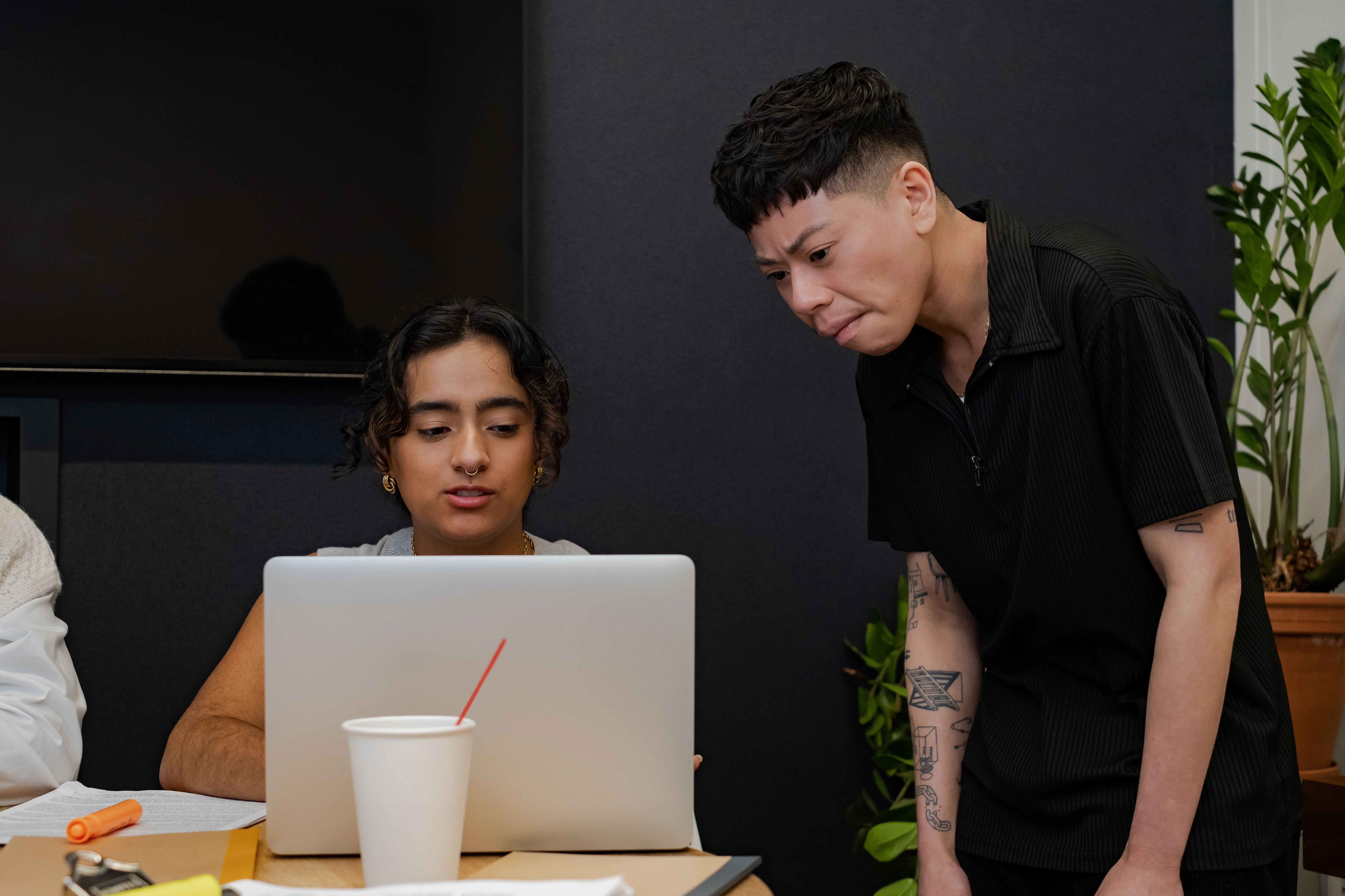 A trans man showing a non-binary colleague something on a laptop