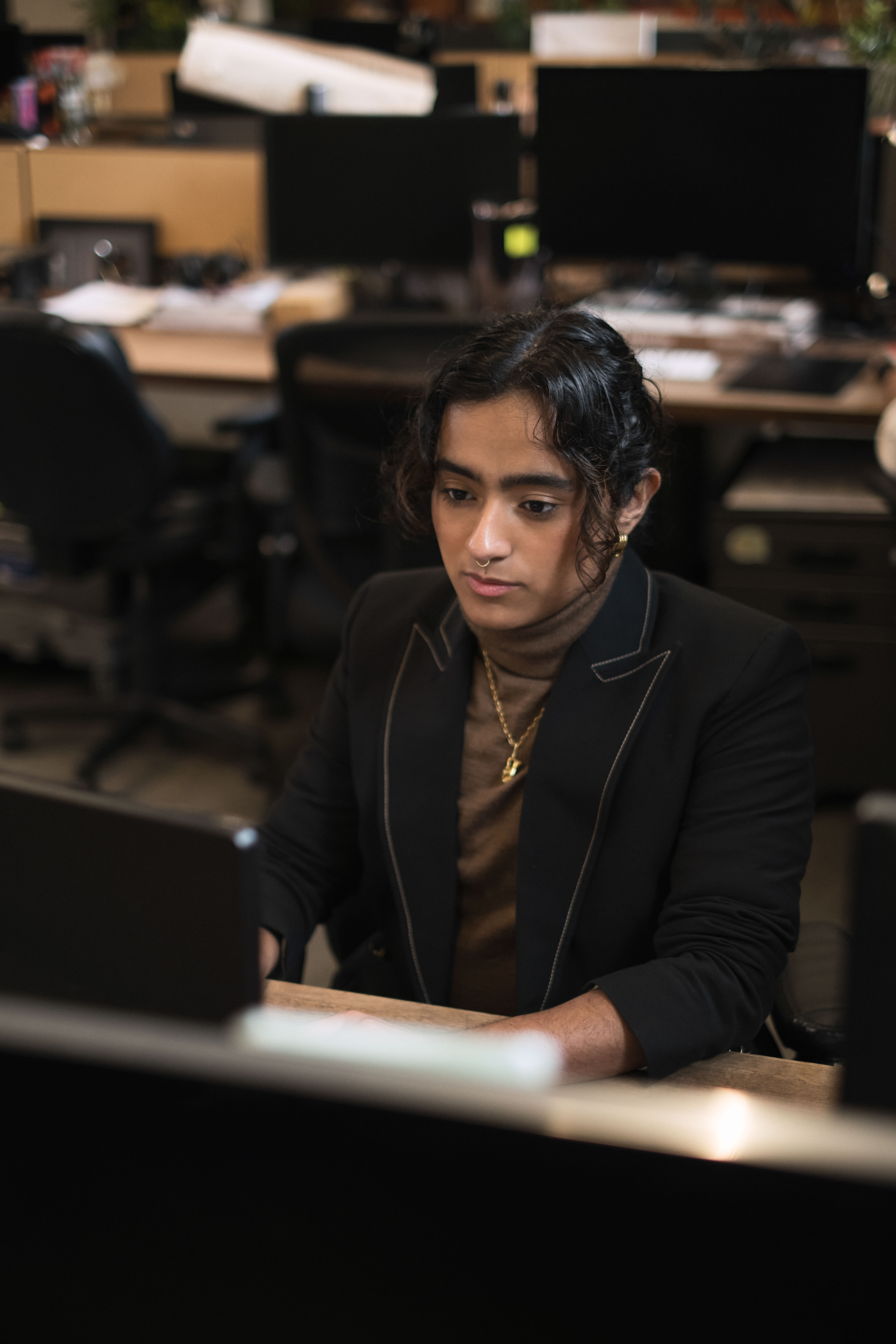A trans man working at a desk in an office