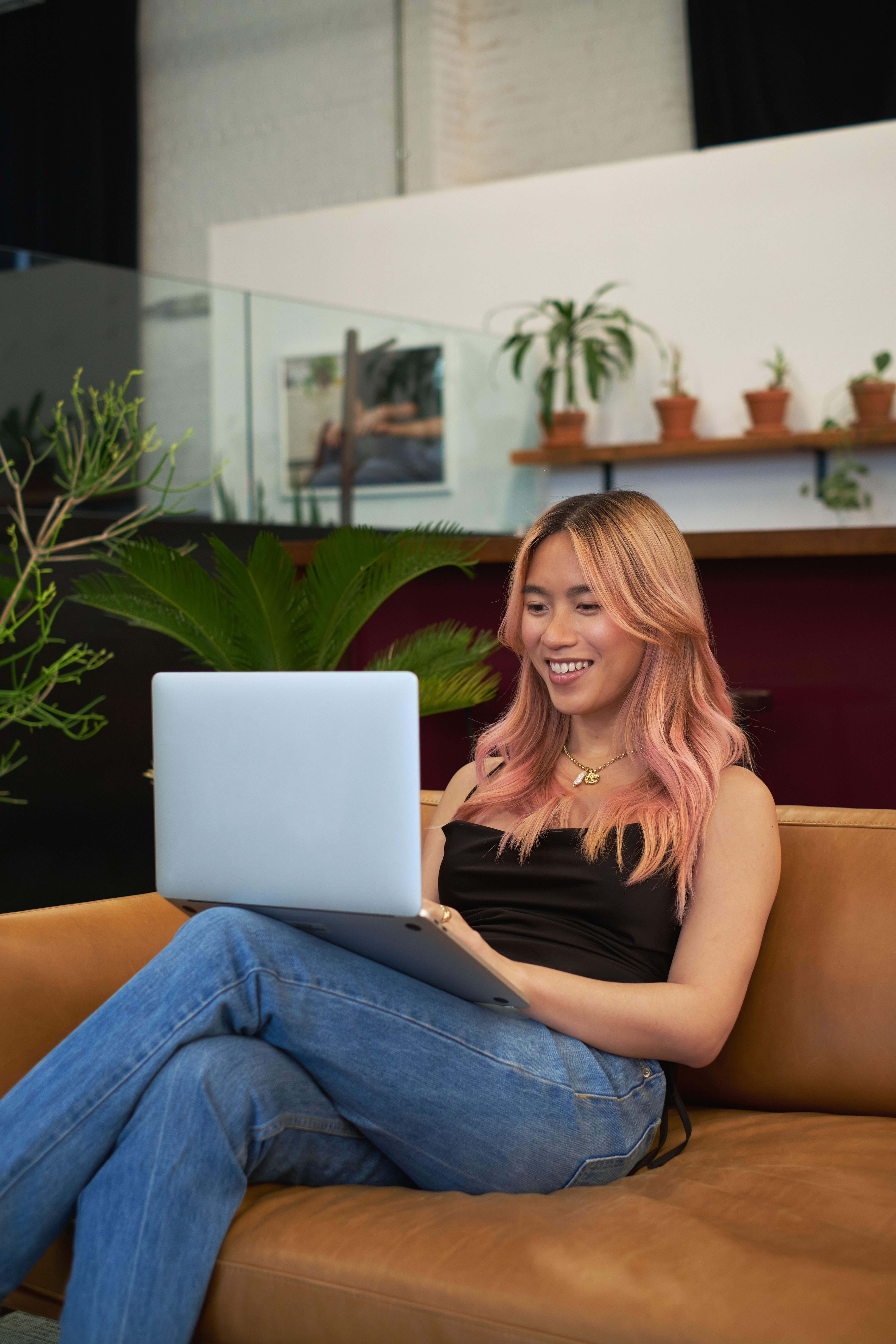 A transfeminine person smiling and using a laptop
