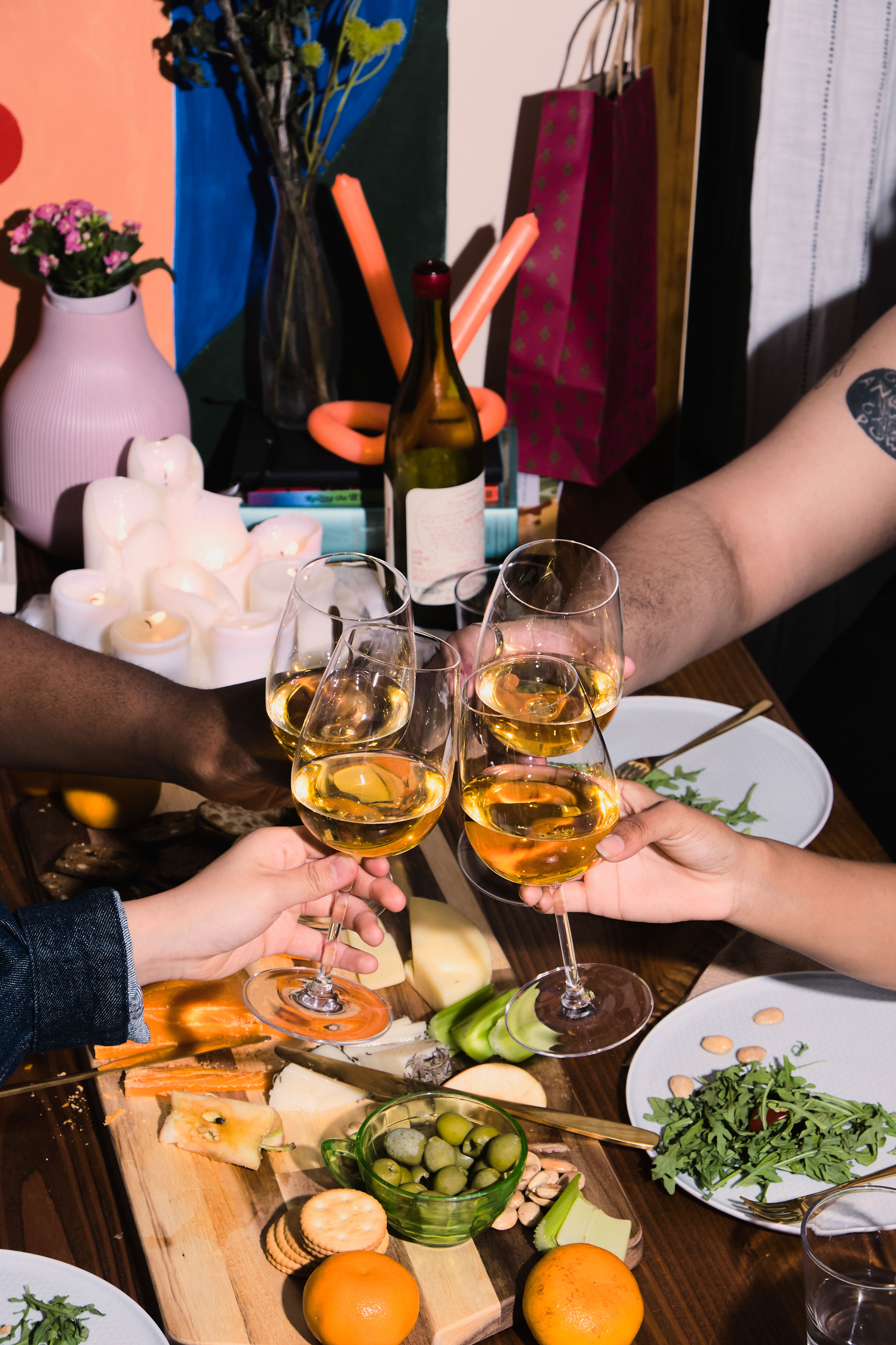 A group of friends of varying genders celebrating at a dinner party