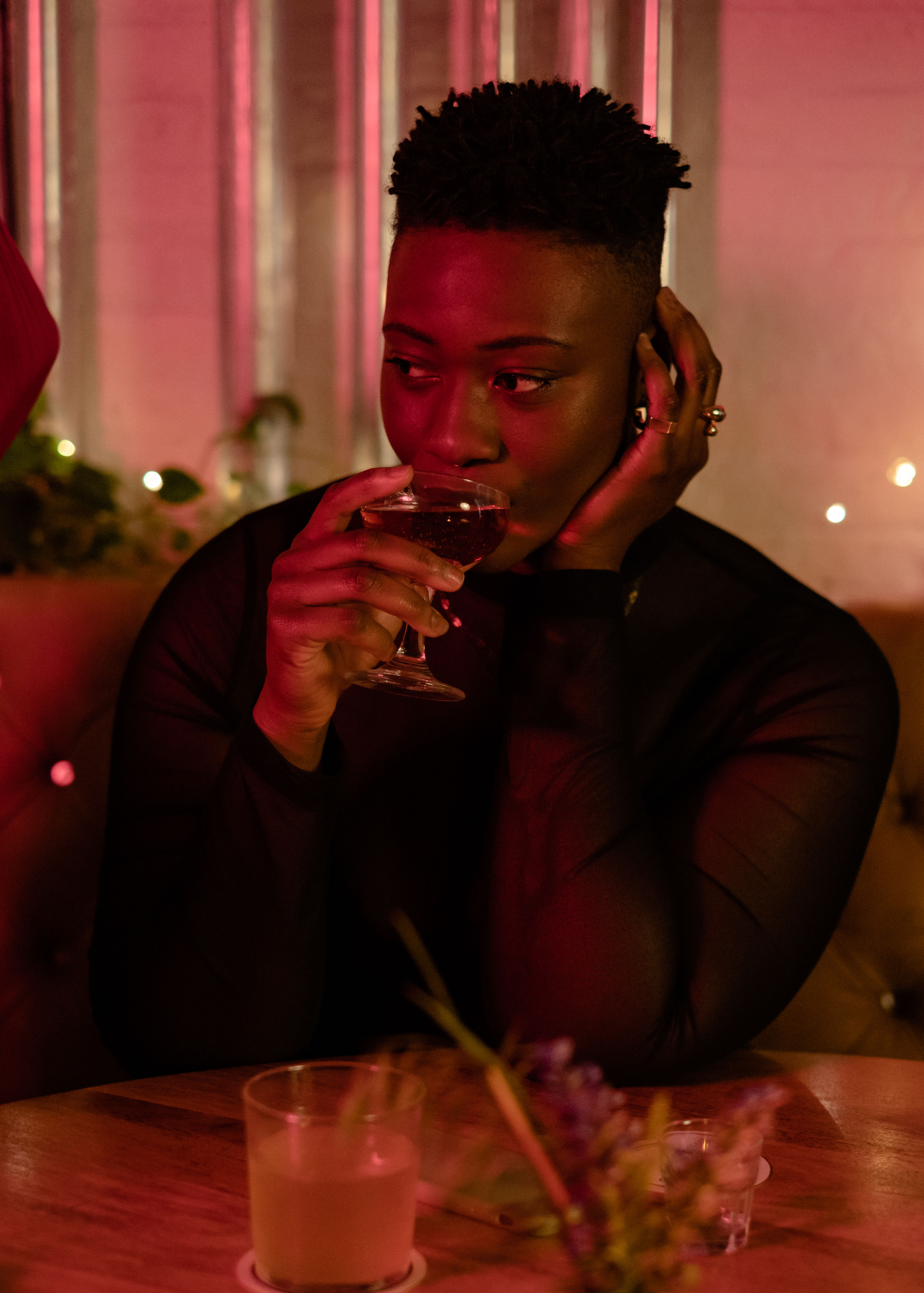 A non-binary person sipping a drink at a bar