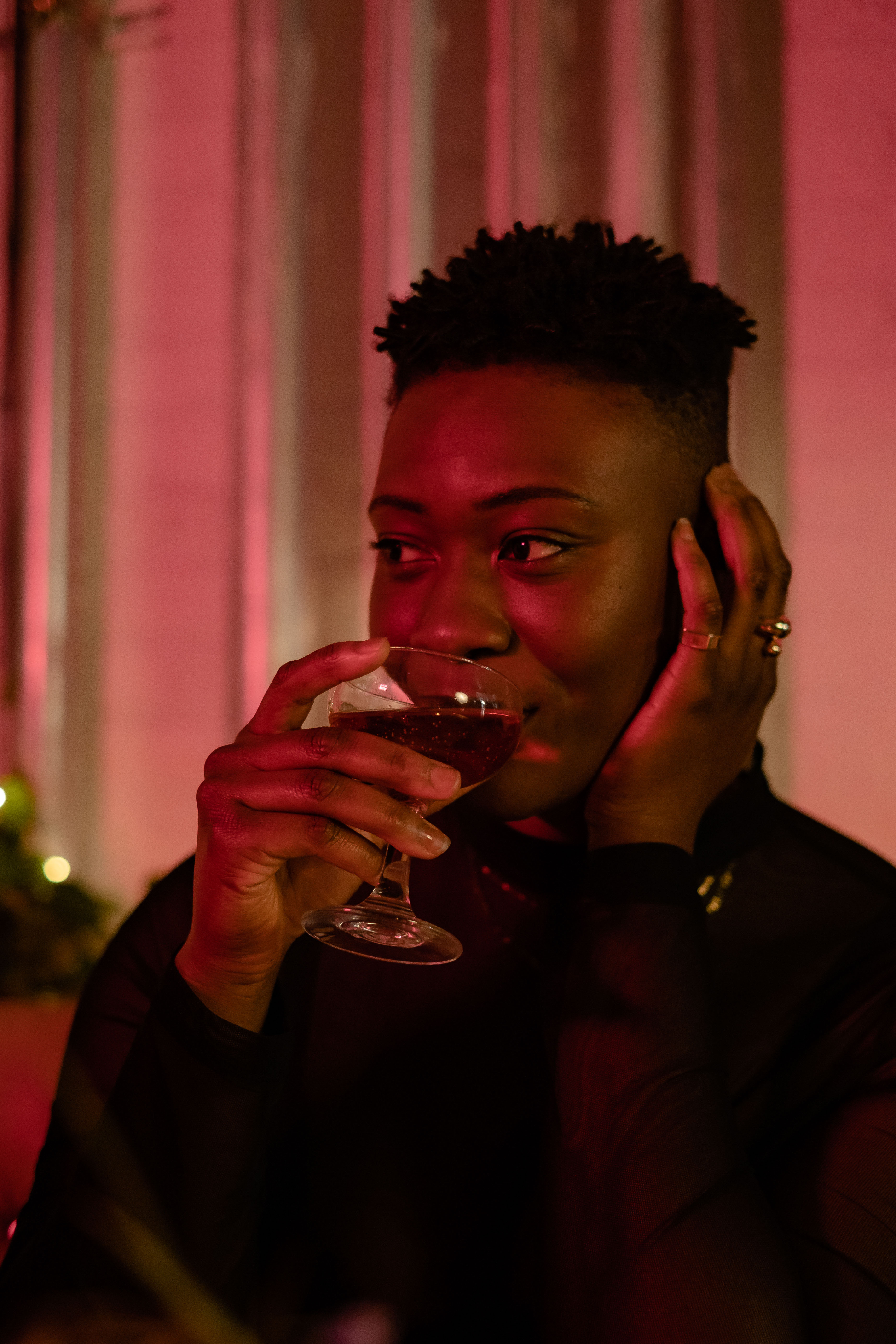 A non-binary person sipping a drink at a bar (1)
