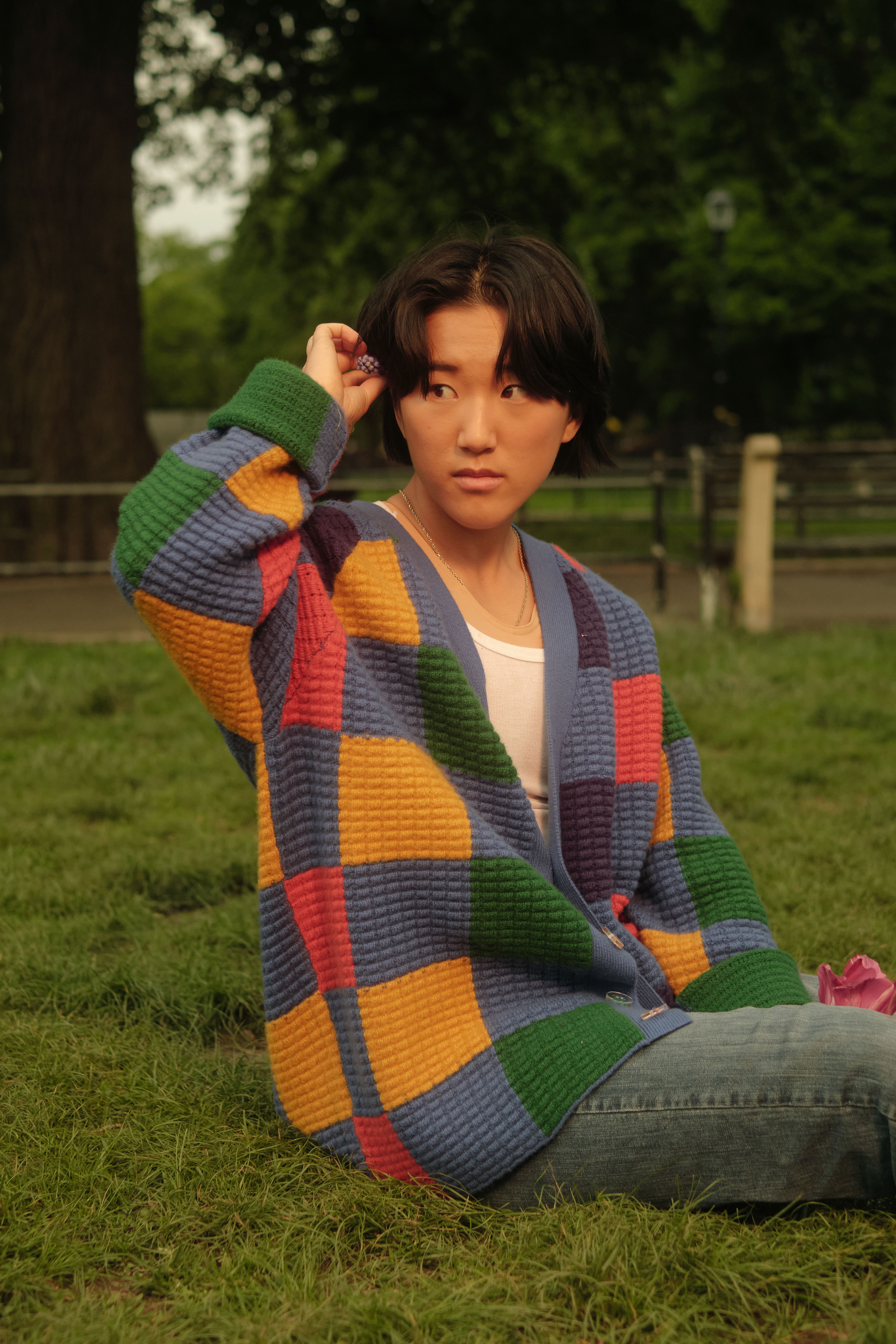A non-binary trans man sitting on grass, holding a flower(1)