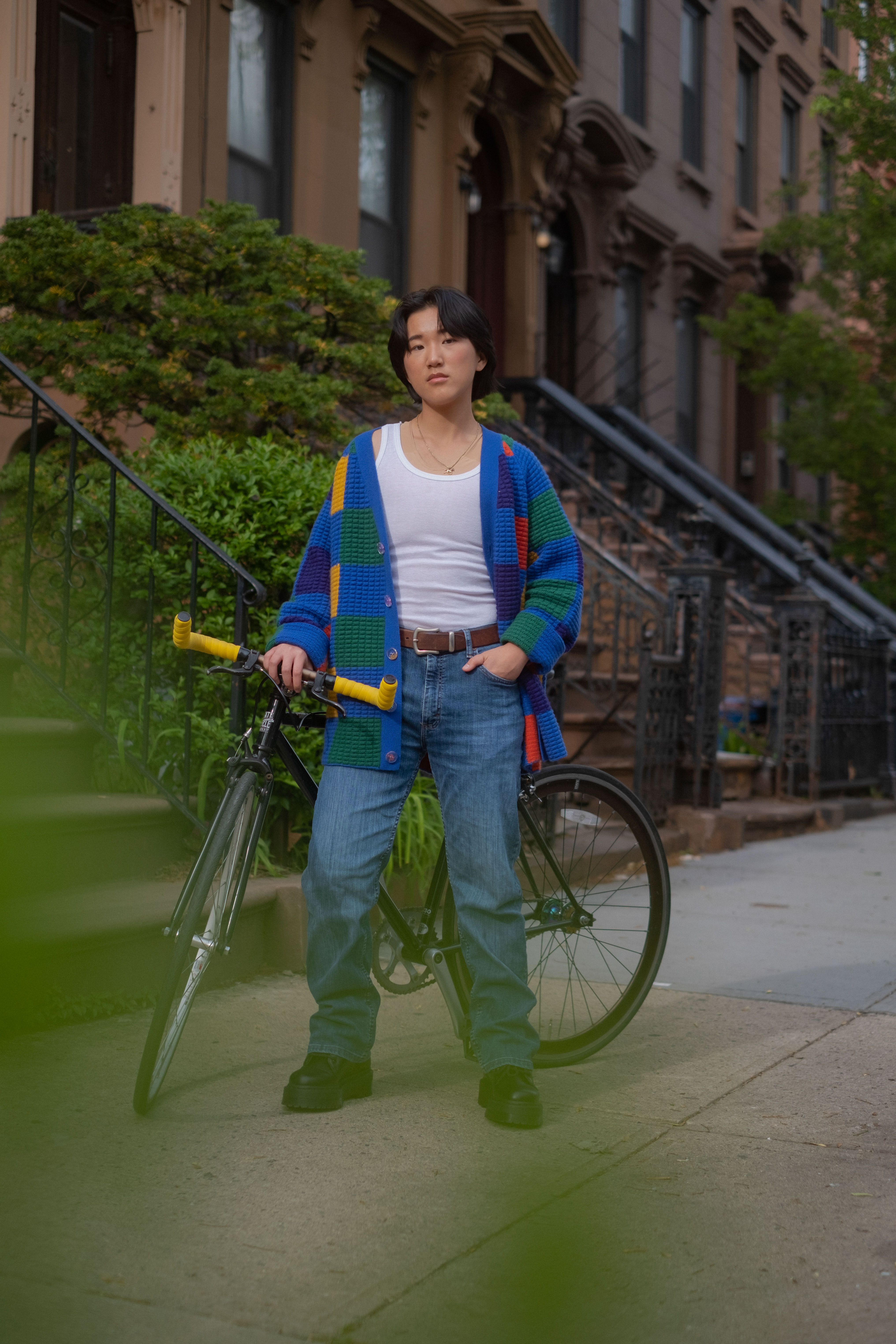 A non-binary trans man standing outside with a bicycle