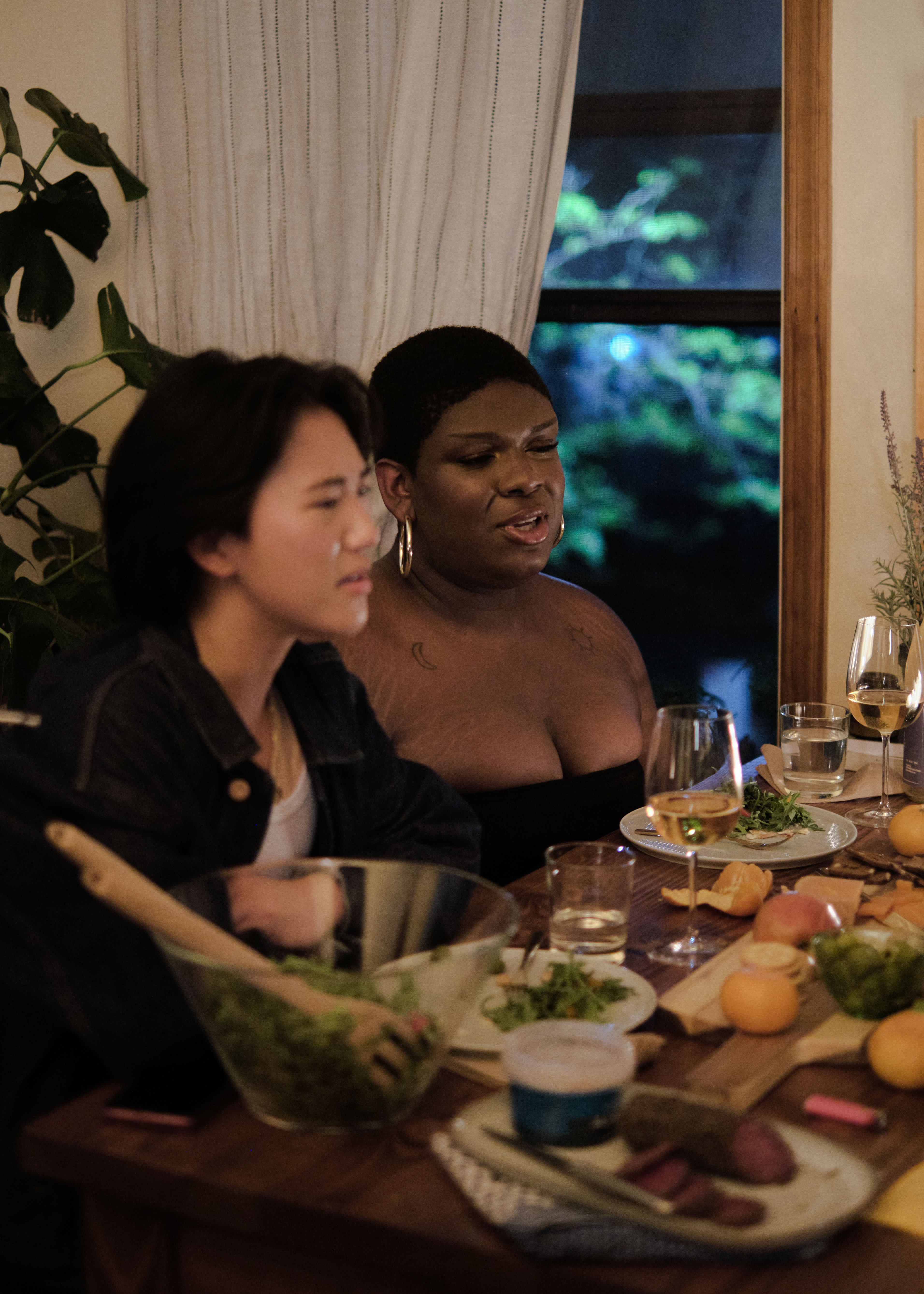 A non-binary trans woman and a non-binary trans man at a dinner party with friends