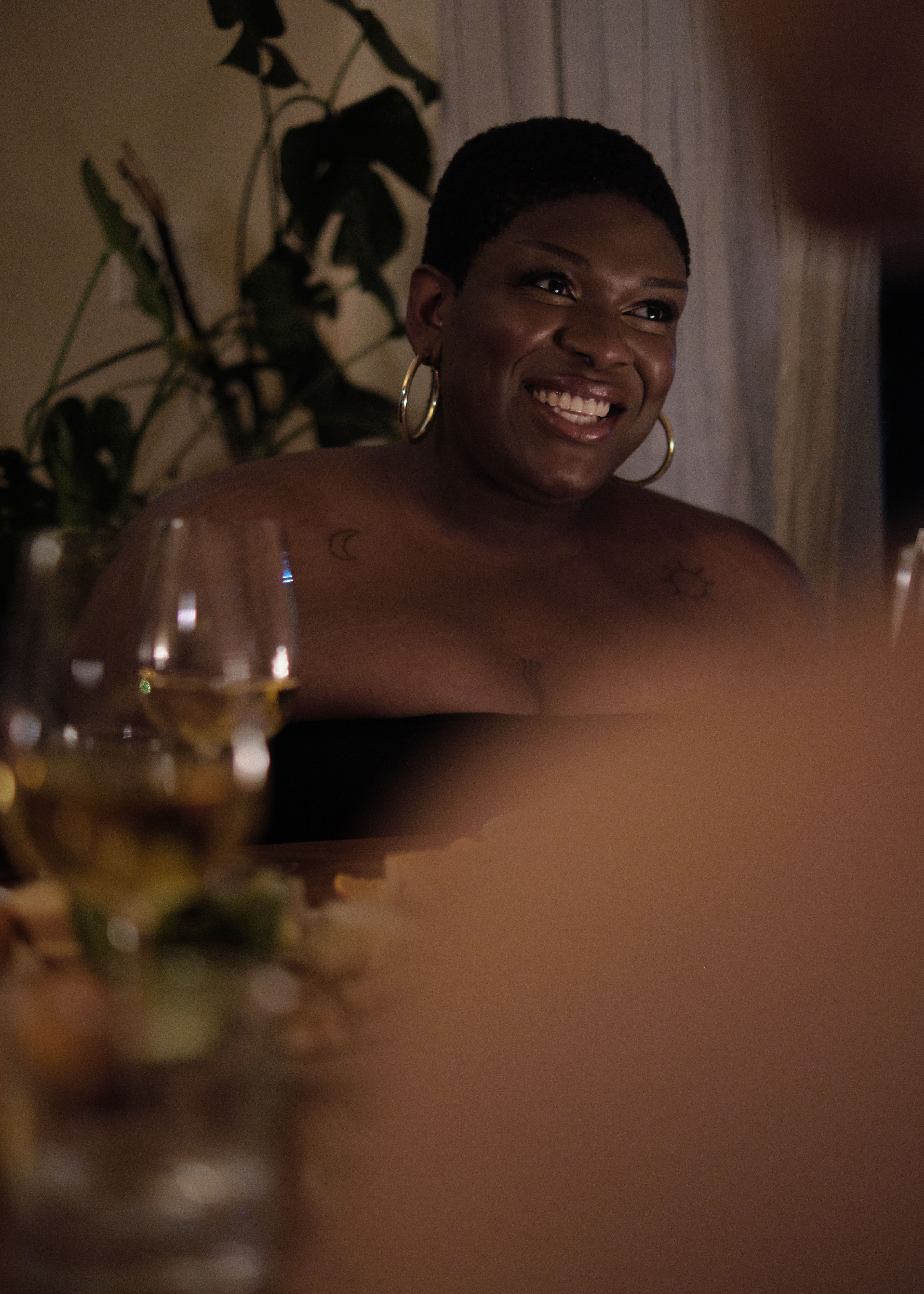 A non-binary trans woman smiling at a dinner party