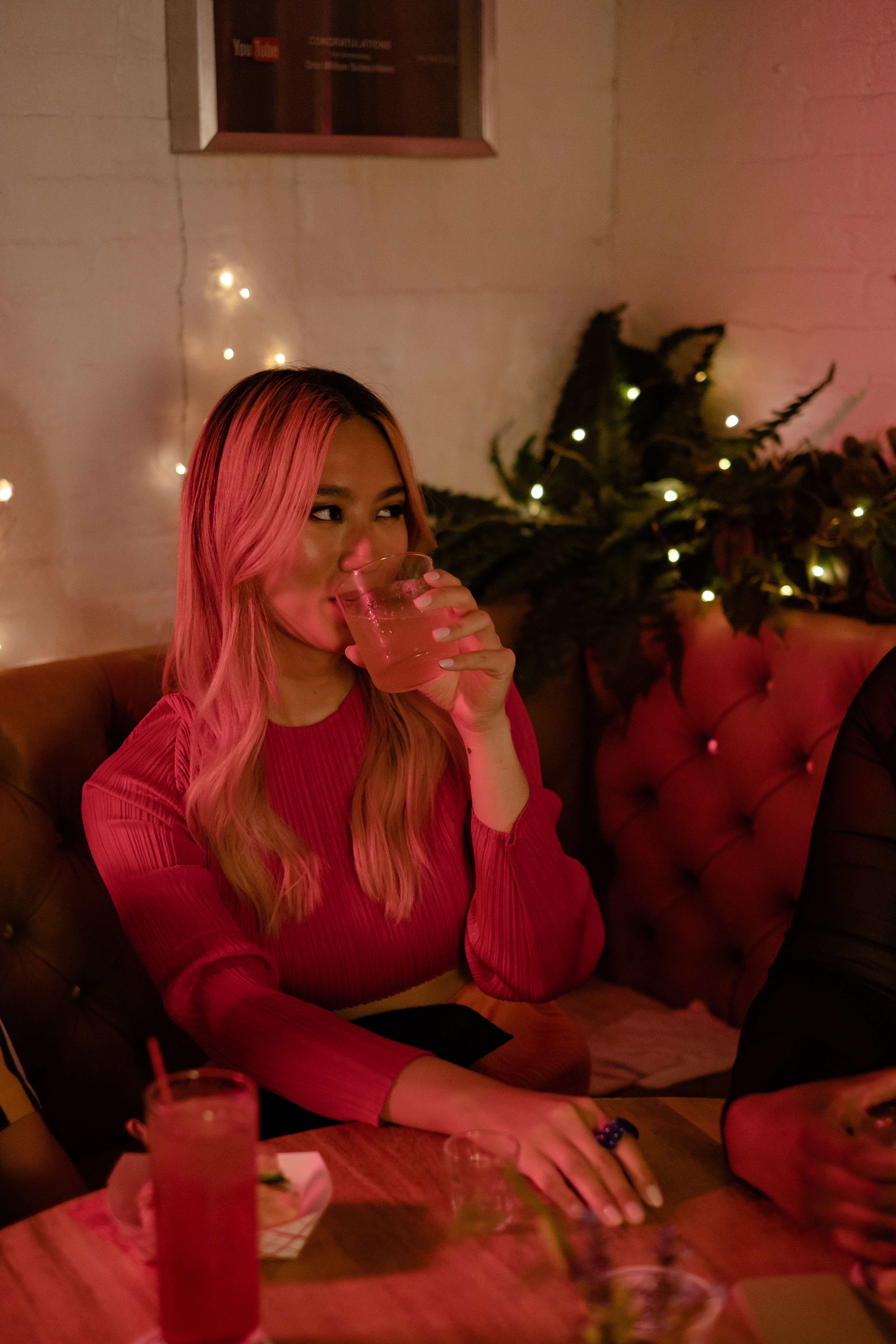 A transfeminine person sipping a drink at a bar