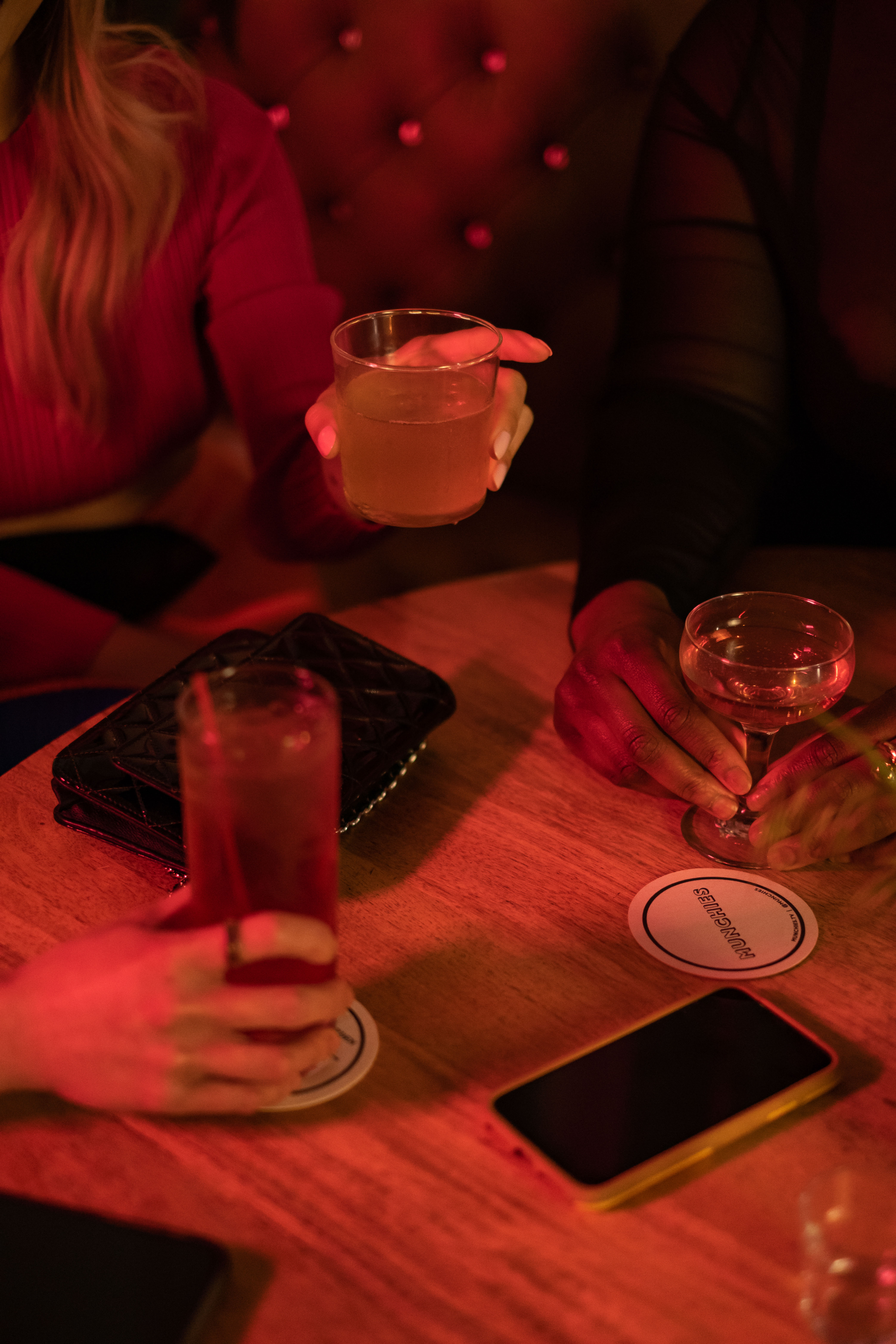 Close-up of a group of friends of varying genders having drinks at a bar