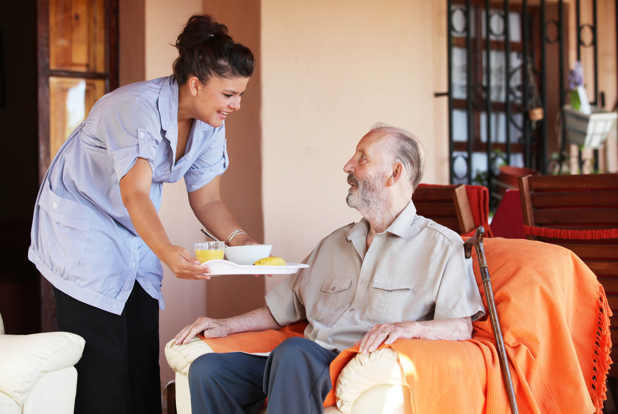 A nurse providing Personalized Home Care New York to a man sitting in an orange chair.