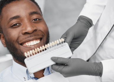 Closeup of a male patient smiling while a dentist holds several prosthetic tooth samples near his mouth.