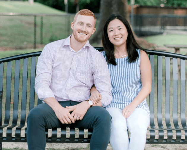 Dr. Josh Dorsett and Dr. Maria Dorsett smiling and sitting next to each other on an outdoor bench.