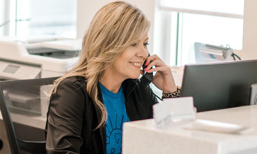 A Dorsett Dental Care staff member talking on the phone and smiling at her computer monitor.