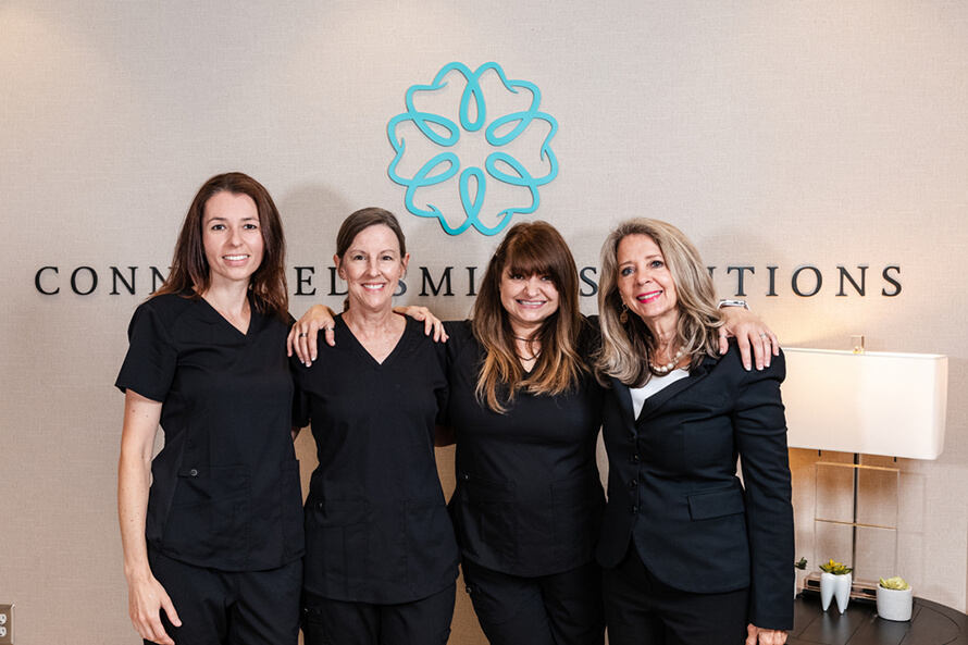 Four Connected Smile Solutions staff members standing at the front desk and smiling.