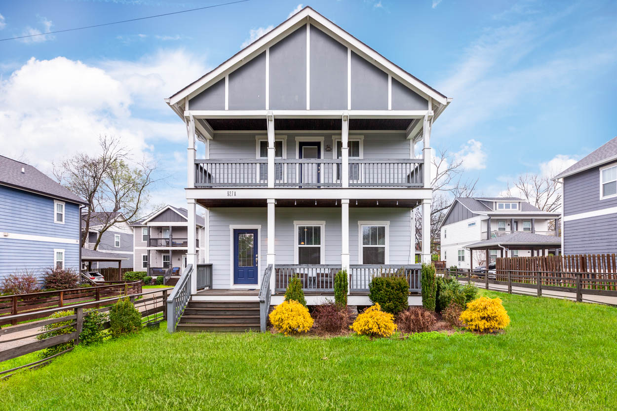 An image of a two story blue grey house with a beautiful grassy lawn and a porch.
