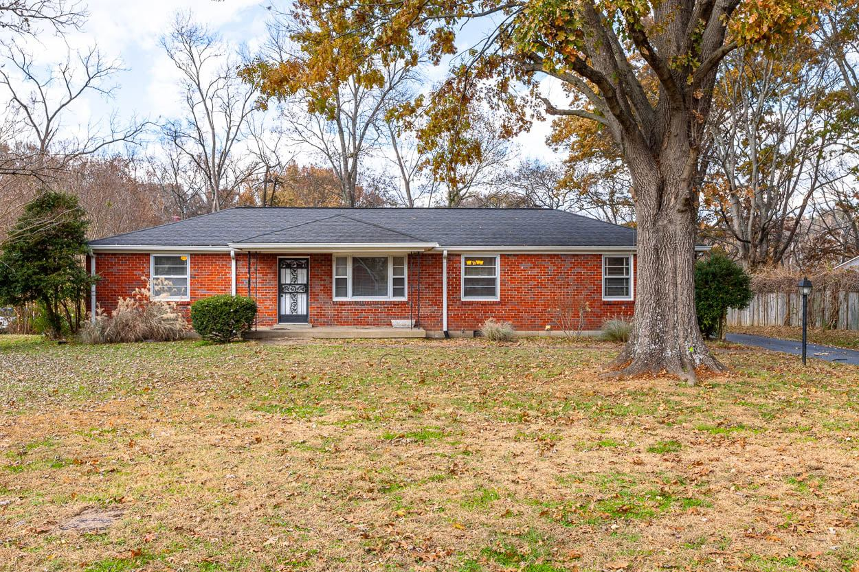 A lovely one story brick home with a cozy porch surrounded by trees.