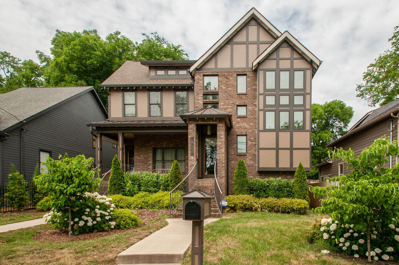 A two story brick house with a wonderful green lawn full of flowers and grass.