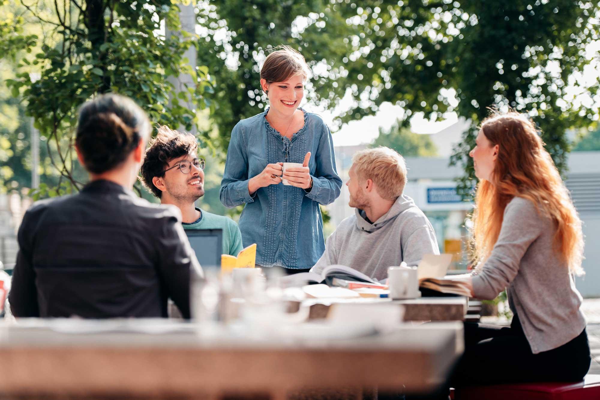 Sommerliche Situation im Freien –4 Studenten sitzen am Tisch, eine lächelnde Frau steht, mit einer Tasse Kaffe in der Hand und lächelnd, hinter dem Tisch. DIe Blicke sind auf sie gerichtet.
