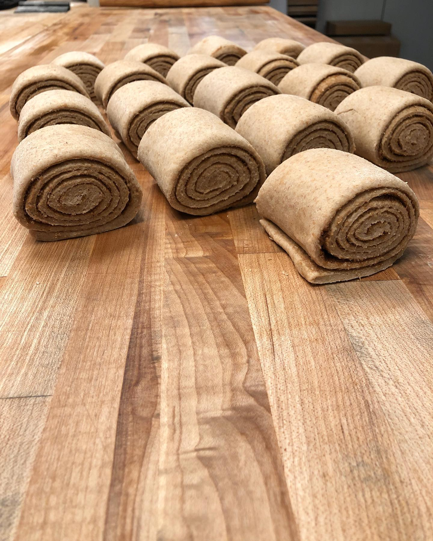 vegan cinnamon buns being rolled ready for baking