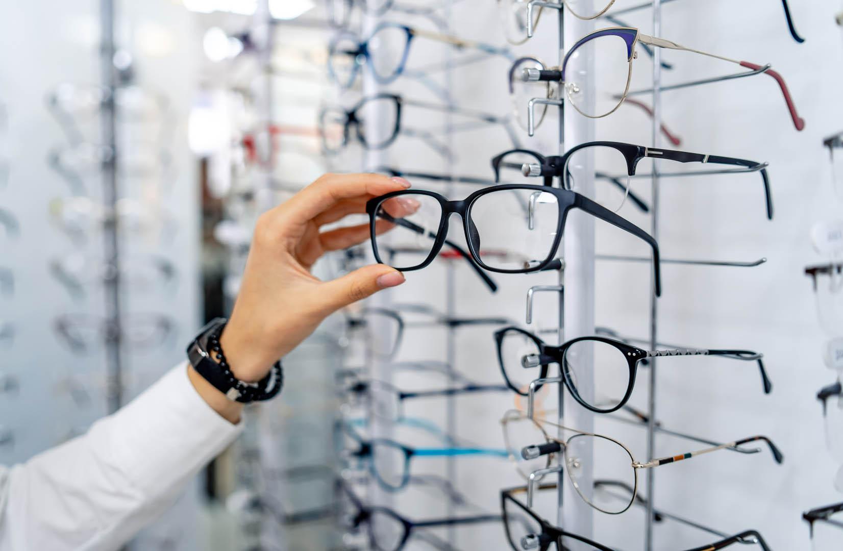 Bilde av en person som velger ut briller fra et brillestativ.