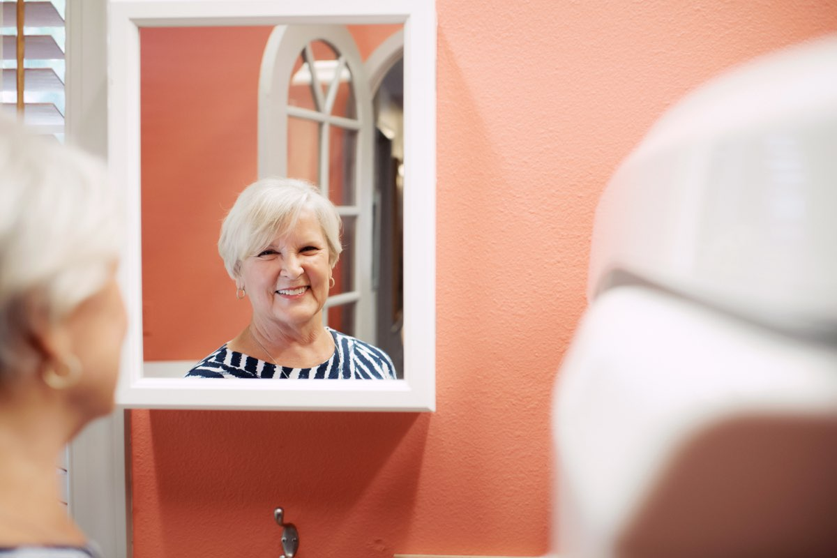 Photo of a patient smiling into a mirror